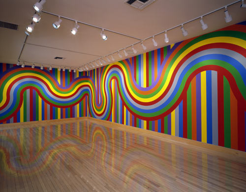 brightly colored lines painted on the wall of a gallery