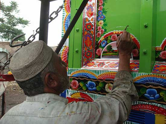 artisan working on elaborately decorated truck