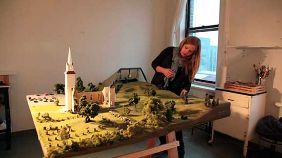 Artist Amy Bennett and one of her landscape model sculptures