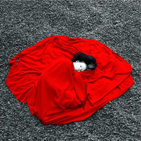 Aida Muluneh photograph of woman lying on ground in billowing red garment